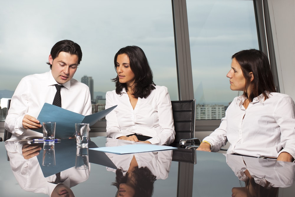 Three people having a meeting by a big city window.